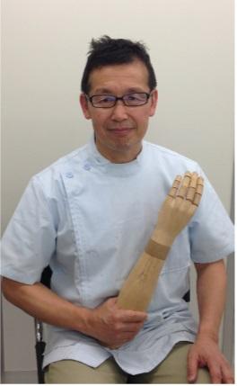 木製義手の模型を持った佐藤専務
